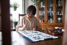 Female Artist Brush Painting Japanese Calligraphy At Dining Table