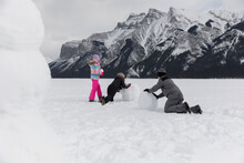 Family Making Snowman In Mount...