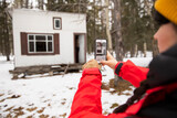 Young woman photographing cabin in woods in snow