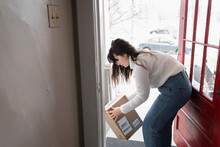 Woman Receiving Parcel At Fron...