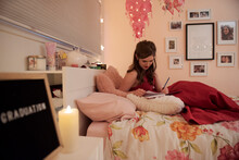 Teenage Girl Writing In Diary On Bed At Home