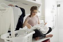 Teenage Girl Folding Laundry I...
