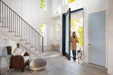 Woman And Dog Entering Modern House Front Door