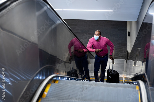 African American wearing covid19 coronavirus mask standing on escalator