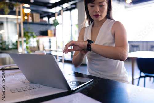 Asian business woman looking her digital watch in office