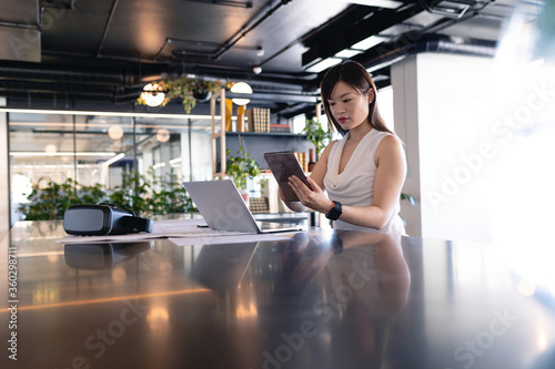 Asian business woman using digital tablet in office