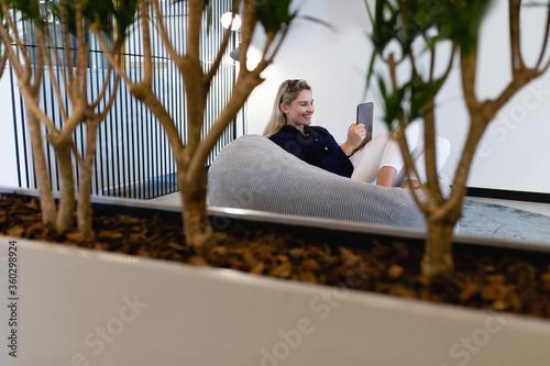 Caucasian woman using a digital tablet in a bean bag