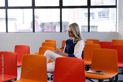 Caucasian woman writing in a conference room