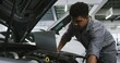African American male car mechanic looking at an open car engine and using a laptop