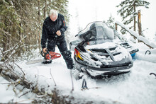 Retired Man Using Chainsaw To Clear Trails While Snowmobiling.
