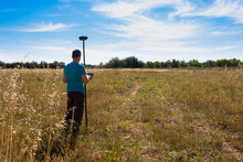 Surveyor Working With A GPS Instrument, Taking Data From The Surface