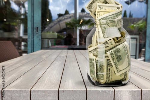 Glass jar with much of dollars money Wallpaper Mural