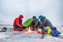 Three Climbers Warm Their Hand...