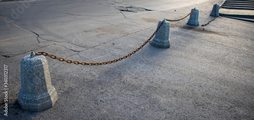Granite pillars was inlaid with a black metal chain between them isolated on the background of the road Tapéta, Fotótapéta