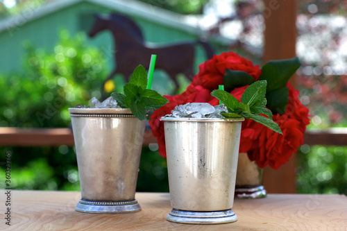Canvas-taulu Mint julep drinks in silver cups with red roses and horse silhouette in backgrou
