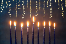 Burning Blue Candles On A Jewish Menorah At Hanukkah With Glittering Bokeh String Lights Behind It