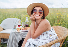 Sincerely Smiling At Camera Young Woman In Sunglasses And  Straw Hat Dressed Light Summer Dress Sitting In Rattan Chair On The High Green Grass Meadow Near Picnic Table Cheerful.Natural Beauty Concept