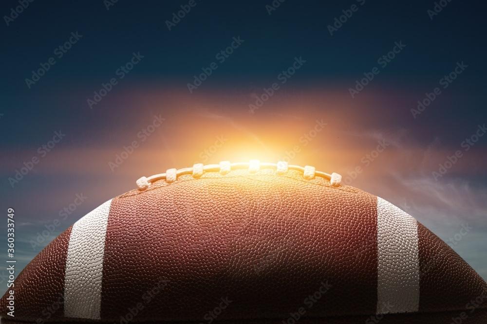 Fototapeta American leather football ball on sky background