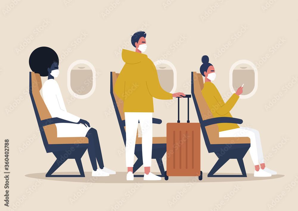 Fototapeta Covid-19, pandemic, coronavirus,  passengers wearing protective masks on board, a side view of an airplane cabin