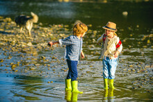 Kids Playing By The Stony River. Summer Activities For Children. Little Boy And Girl Throws Stones Into The Water On The Shore Of A Lake Or River.