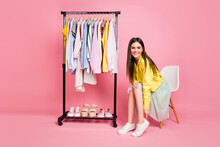 Full Length Photo Of Pretty Lady Showroom Fashion Collection Choosing Clothes Put On Cool Shoes Sit Chair Wear Yellow Leather Jacket Long Skirt Isolated Pastel Pink Color Background
