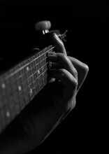 Close-up Of A Guitarist's Hand, Chord. Guitarist Male Hands. The Musician's Fingers On The Strings Of An Acoustic Guitar Pinch A Chord In Black And White.