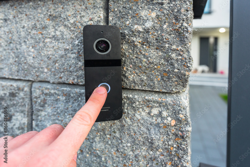 Fototapeta Hand pressing button of video intercom mounted on the stone wall