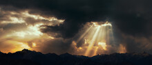Rays Of Light Shining Through Dark Clouds Over Mountains. Cinematic Scene.