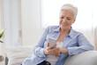 Modern Technologies For Seniors. Smiling Elderly Lady Using Smartphone At Home