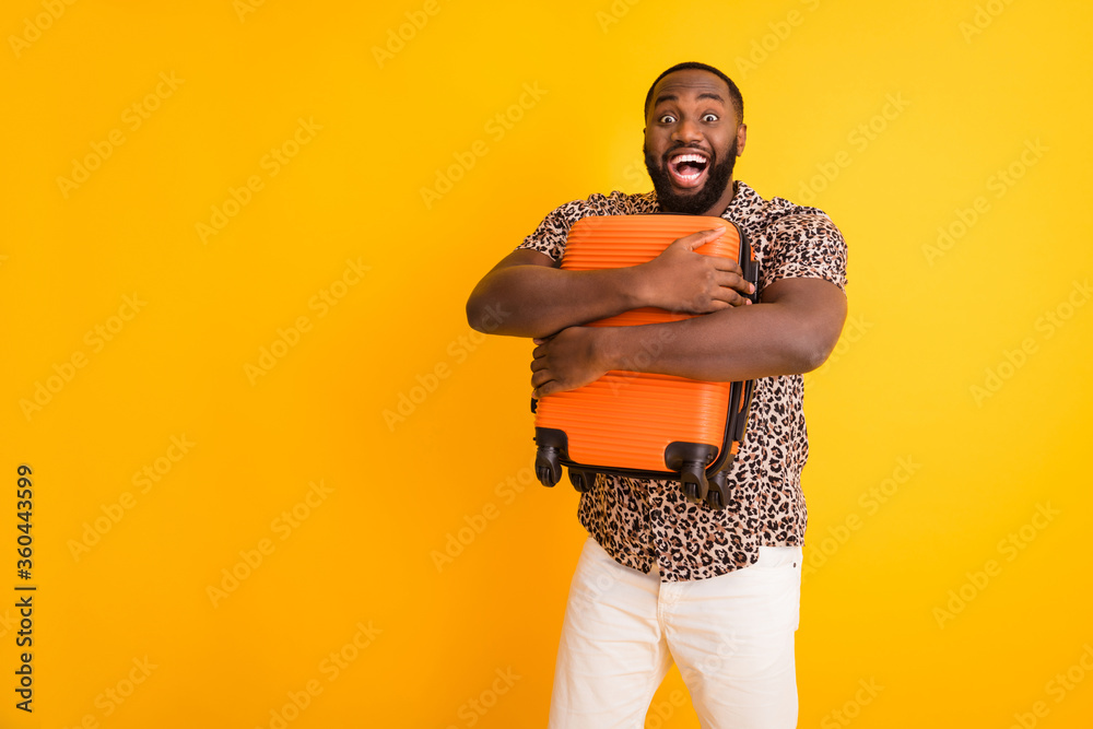Fototapeta Portrait of his he nice handsome overjoyed crazy bearded cheerful cheery guy holding in hands hugging luggage departure exotic tour rest isolated on bright vivid shine vibrant yellow color background