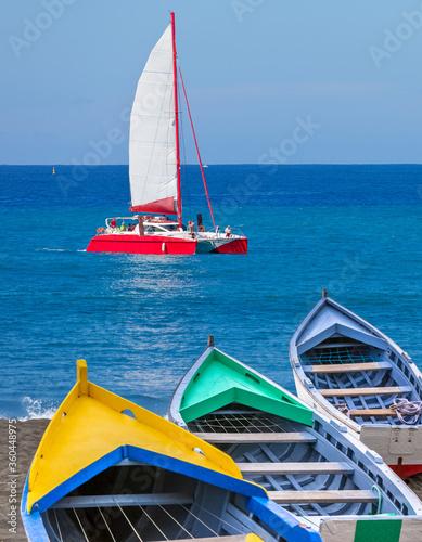 Catamaran en mer et barques de pêche sur plage en baie de Saint-Paul, île de la Wallpaper Mural