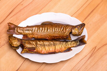 Two Smoked Fish On A White Plate - Two Smoked Fish, Brook Trout, On A White Plate On A Beech Table.