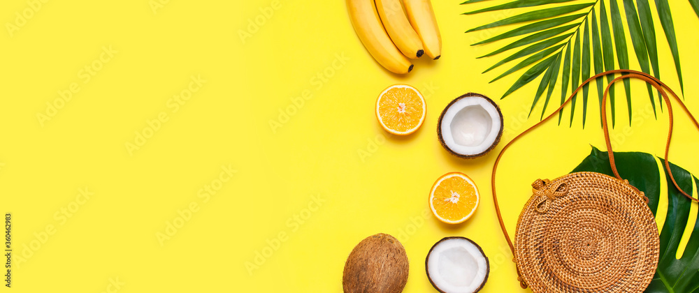 Fototapeta Summer fashion flat lay. Round trendy rattan bag, tropical palm leaves, coconut, orange, bananas on yellow background. Top view, copy space. Trendy bamboo bag. Creative background, vacation concept