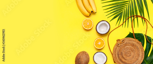 Summer fashion flat lay. Round trendy rattan bag, tropical palm leaves, coconut, orange, bananas on yellow background. Top view, copy space. Trendy bamboo bag. Creative background, vacation concept