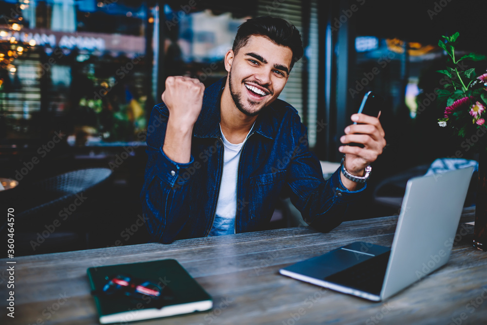 Fototapeta Cheerful hipster guy looking at camera excited with getting good news checking email on smartphone, portrait of happy male freelancer celebrating success of completed project sending message to friend
