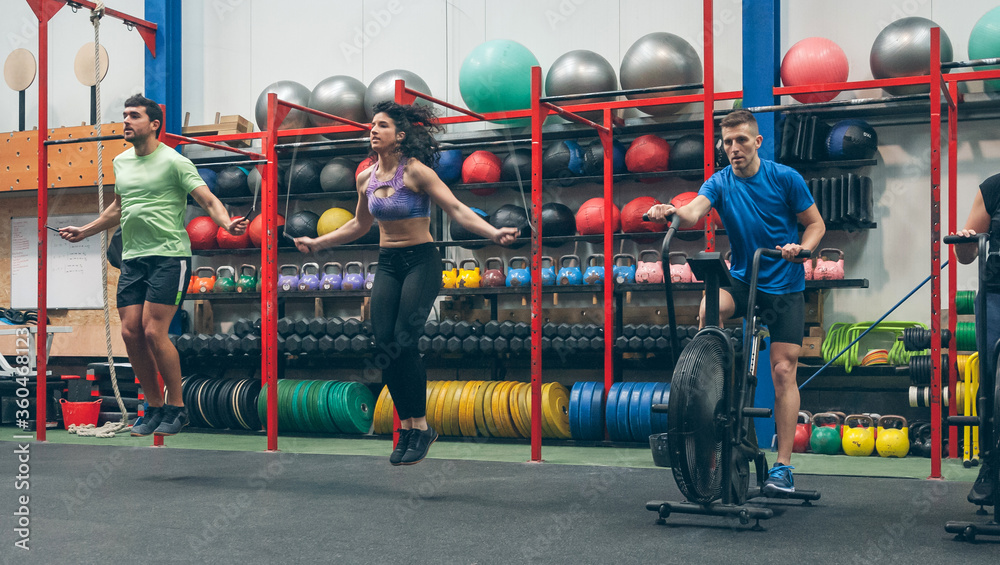 Fototapeta Group of athletes doing air bike and skipping rope at the gym
