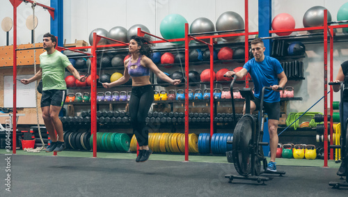 Fototapeta Group of athletes doing air bike and skipping rope at the gym obraz