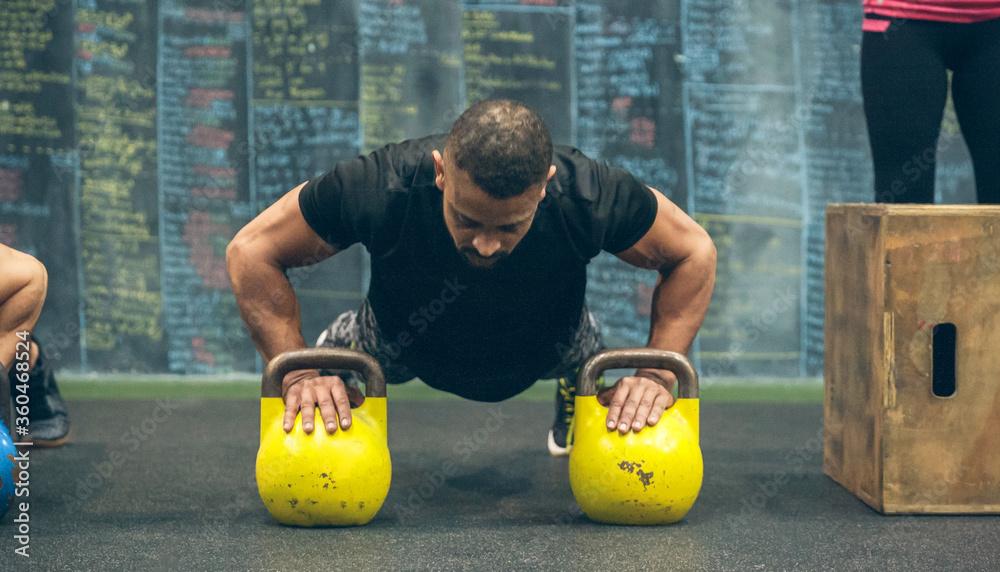 Fototapeta Sportsman doing push-ups with kettlebells in the gym