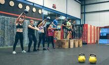 Sportswomen Exercising With Ke...