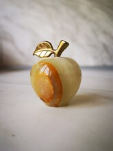 Shot Of A Brown Marble Apple With Gold Stem Presented On The Floor