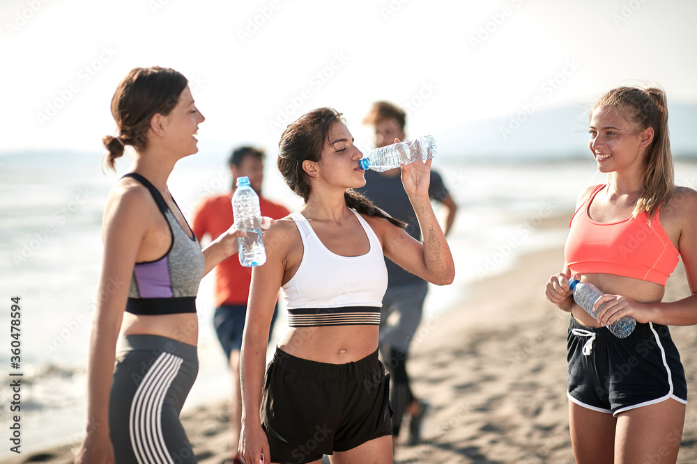 Fototapeta Young fitness womans drinking water by the sea.