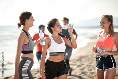 Fototapeta Young fitness womans drinking water by the sea. obraz