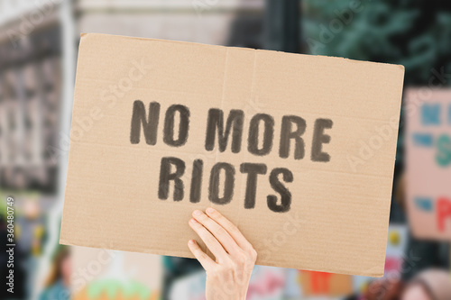 The phrase  No more riots  on a banner in men's hand with blurred background Canvas Print