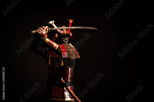 Fototapeta Portrait of a samurai in armor in attack position obraz