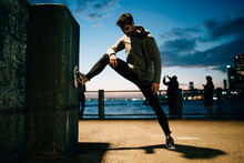 Sportsman Dressed In Tracksuit Doing Stretching While Enjoying Music During Evening Workout In Urban Setting.Young Man In Sport Wear Doing Exercise Training Outdoors While Listening Audio In Earphones