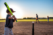 Caucasian Boy With Baseball Bat At Home Plate Ready To Hit A Ball Off A Tee