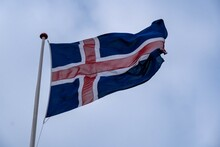 Low Angle Shot Of The Flag Of Iceland Dancing Freely In The Wind Under The Blue Sky