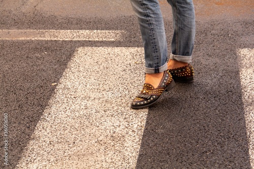Person crossing an asphalt street wearing modified shoes with pins on them and b Wallpaper Mural