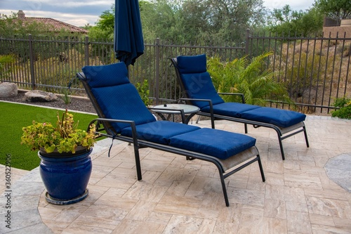 Blue lounge chairs on a travertine spa deck.