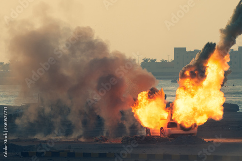 Fotografering Close up of a Military strike or bomb in war on an SUV with tanks causing fire balls and explosion in the town in chaos